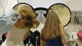 As mulheres da vista inferior vêm espelhar nos vidros formam com sacos filme