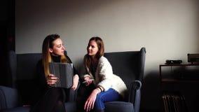 As mulheres de fascínio usam a tabuleta e o bate-papo durante o almoço e sentam-se em poltronas cinzentas no escritório à moda du vídeos de arquivo