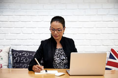 As mulheres de negócio asiáticas bonitas estão trabalhando com o portátil no café Fotos de Stock Royalty Free