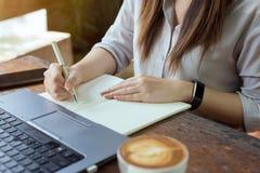 As mulheres de negócio que usam o portátil e notam alguns dados no bloco de notas fotografia de stock