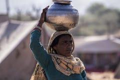 As mulheres de Pushkar tomam a água de uma bacia da água fotografia de stock