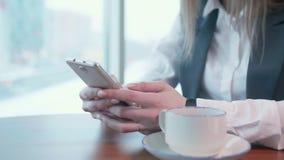 As mulheres de um negócio novas que trabalham no whith do café telefonam filme