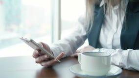 As mulheres de um negócio novas que trabalham no whith do café telefonam video estoque