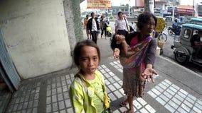 As mulheres desabrigadas que afagam a criança imploram pela esmola video estoque