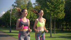As mulheres desportivas ativas da aptidão que correm no verão estacionam video estoque