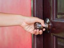 As mulheres do close up estão abrindo a porta de madeira marrom foto de stock royalty free