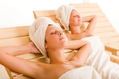 As mulheres do quarto dois dos termas da beleza relaxam sol-camas imagem de stock royalty free