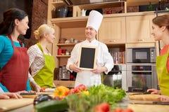 As mulheres e o cozinheiro chefe felizes cozinham com menu na cozinha Fotos de Stock
