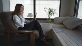 As mulheres em um hotel que falam na tabuleta com família vídeos de arquivo