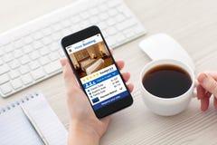 As mulheres entregam guardar o telefone com reserva de hotel do app na tela imagens de stock royalty free