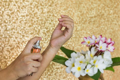 As mulheres entregam o perfume de pulverização no pulso com as flores no vaso e no cl Imagem de Stock Royalty Free