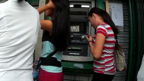 As mulheres estão em uma fila para usar o ATMs de um banco, sinal avariado visível video estoque