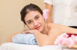As mulheres estão encontrando-se na cama pronta para tomar sobre o curso dos termas com o terapeuta da massagem foto de stock