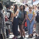 As mulheres estão esperando amigos perto do jardim de Covent, enterradas nos telefones celulares Imagens de Stock
