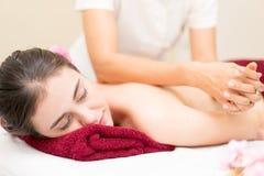 As mulheres estão obtendo-a fazem massagens para trás em uma cama Foto de Stock