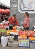 As mulheres estão vendendo frutos no mercado em Lijiang foto de stock