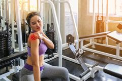 As mulheres exercitam já doloroso Fêmea asiático tendo a dor em seu braço quando exercício no gym Dor forte do sentimento fêmea d fotografia de stock royalty free