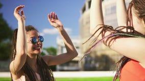 As mulheres felizes com temem sentar-se na grama no parque do verão Amigos novos que falam, dançando e jogando fora ter o diverti video estoque