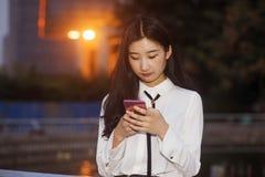 As mulheres felizes usam telefones celulares para consultar a Web Fotografia de Stock Royalty Free