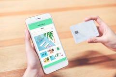 As mulheres guardam o smartphone e a loja em linha de compra do cartão de crédito Foto de Stock