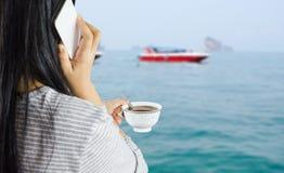 As mulheres guardam a xícara de café e a fala no móbil ou no smartphone em Imagens de Stock Royalty Free