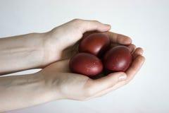 As mulheres irreconhecíveis entregam a sustentação de três ovos Batendo um ovo da páscoa vermelho Tradição velha do feriado Isola fotografia de stock royalty free
