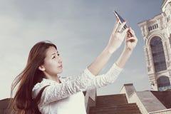 As mulheres japonesas novas com cabelo longo fazem o selfie dentro Imagem de Stock