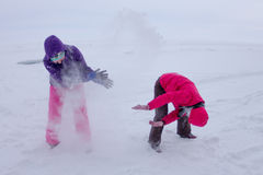 As mulheres jogam na neve durante uma queda de neve no gelo do lago Baik Foto de Stock