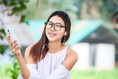As mulheres jogam o telefone no parque e vestem o vestido branco É fone de ouvido do sorriso e do desgaste fotografia de stock