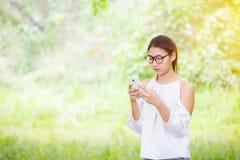 As mulheres jogam o telefone no parque e vestem o vestido branco fotografia de stock royalty free