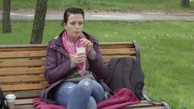 as mulheres 4K no revestimento sentam-se no banco no parque e bebem-se a bebida quente através da palha filme