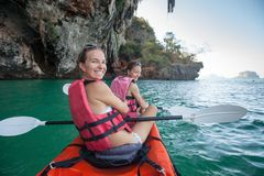As mulheres kayaking nas cavernas do mar na costa de Krabi, Tailândia Fotografia de Stock