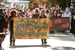 As mulheres levam a bandeira que começa a parada do Dia das Bruxas Fotos de Stock Royalty Free