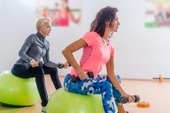 As mulheres magros desportivas que participam na classe da aptidão do gym que exercita o assento nos physioballs que fazem os bíc foto de stock royalty free