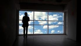 As mulheres mostram em silhueta ao lado da janela e do céu grandes Fotografia de Stock Royalty Free