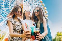 As mulheres multirraciais do retrato do estilo de vida do verão apreciam o dia agradável, guardando vidros dos milks shake Parte  fotografia de stock