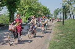 As mulheres na forma velha denominam enjoing e dar um ciclo com a bicicleta do vintage na rua Fotografia de Stock Royalty Free