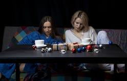 As mulheres na roupa da casa bebem o chá Fundo preto fotografia de stock