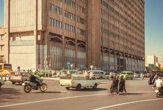 As mulheres no hijab vestem a rua transversal de passeio completamente de carros, de velomotor e de táxi moventes Fotos de Stock