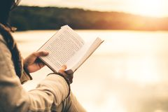 As mulheres no inverno sentam-se leram o livro favorito no feriado imagem de stock