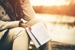 As mulheres no inverno sentam-se leram o livro favorito no feriado fotos de stock royalty free