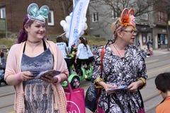 As mulheres no traje da Páscoa distribuem presentes às crianças ao longo do leste da rua da rainha na parada 2017 da Páscoa das p Imagem de Stock