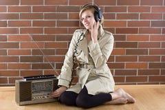As mulheres no trenchcoat escutam um rádio do vintage imagens de stock royalty free