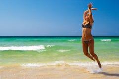 As mulheres novas saltam na praia imagem de stock royalty free