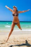 As mulheres novas saltam na praia fotos de stock royalty free