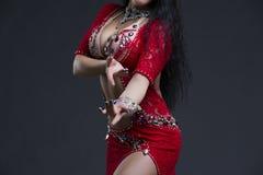 As mulheres orientais exóticas bonitas novas executam a dança do ventre no vestido vermelho étnico no fundo cinzento fotografia de stock royalty free
