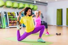 As mulheres que fazem esticando a ioga exercitam na esteira dentro no gym foto de stock royalty free