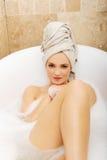 As mulheres que relaxam na banheira? vestiram-se em um bathrobe azul, mais fotos com este modelo no <a href='http://www Foto de Stock Royalty Free