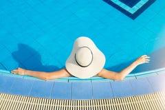 As mulheres que vestem chapéus de palha e relaxam na piscina imagem de stock royalty free