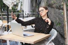 As mulheres que vestem vidros, camisa preta no café estão fazendo o selfie Imagem de Stock